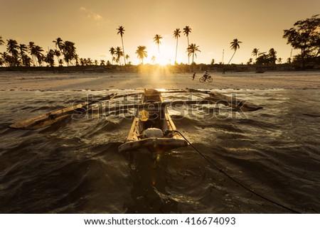 Traditional fishing boat floating on ocean at beautiful sunset in Zanzibar, Tanzania. - stock photo