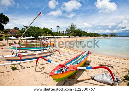 Traditional fishing boats on a beach in Sanur on Bali. Indonesia. - stock photo