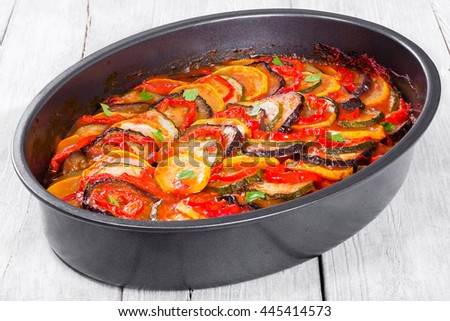 traditional French casserole -  ratatouille: stewed zucchini, red bell pepper, parsley, yellow squash, eggplant, tomato sauce and garlic in baking dish, close-up - stock photo