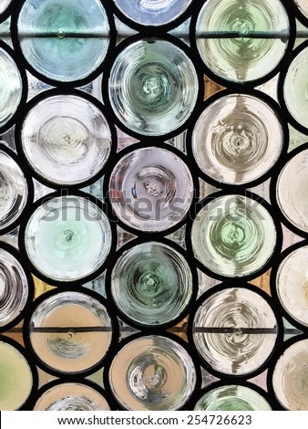 Traditional French chateau window made of circular tinted glass forming an interesting pattern and texture suitable for backgrounds or wallpapers - stock photo