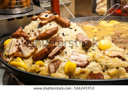 Traditional french dish at Christmas market in Paris - Sauerkraut  cooked in Riesling wine with sausages, meats and potatoes. Selective focus on the upper sausages. - stock photo