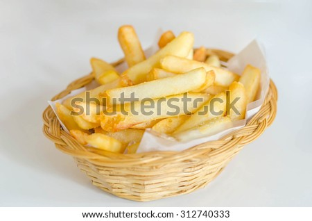 Traditional French fries in a bamboo basket - stock photo