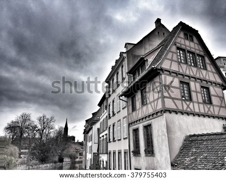 Traditional french houses in Alsace with a cloudy grey sky in background - stock photo