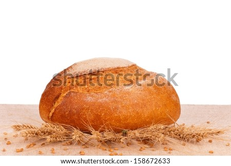 Traditional fresh round white bread on a burlap over white background - stock photo