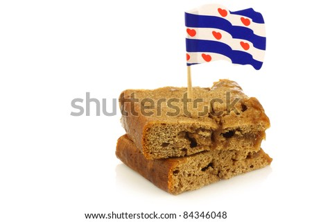 "traditional Frisian pastry called ""Kandijkoek "" with a frisian flag toothpick on a white background - stock photo"