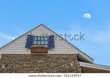 traditional gable house with glass window stone cladding and flower bed under moon sky - stock photo