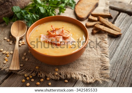 Traditional german homemade pea soup preparation recipe with bacon greens and croutons in clay dish on vintage wooden table background. Tasty national food. Rustic style. - stock photo