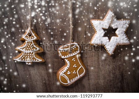 Traditional gingerbread cookies hanging over wooden background - stock photo