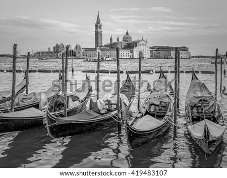 Traditional gondolas with the bell tower of the Saint Giorgio Maggiore Church on background (view from San Marco embankment) - Venice, Italy (black and white) - stock photo