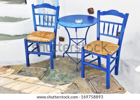 Traditional greek terrace with blue tables and chairs in Pyrgos, Santorini, Cyclades, Greece - stock photo