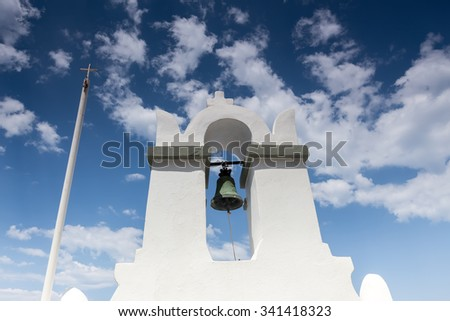 Traditional Greek white church arch with cross and bells in village Fira of Cyclades Island Santorini Greece. Close up - stock photo