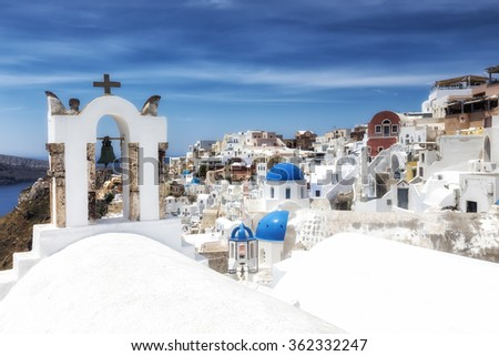 Traditional Greek white church arch with cross and bells in village Oia of Cyclades Island Santorini Greece - stock photo