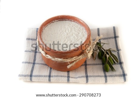 Traditional greek yogurt in a brown ceramic pot on white background - stock photo