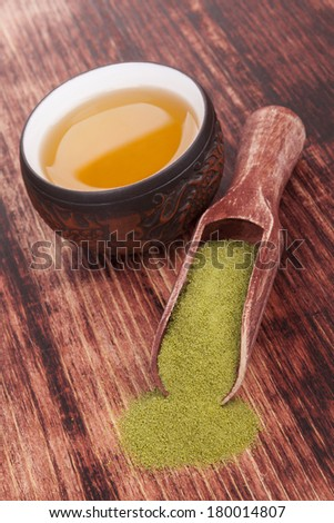 Traditional green powdered tea matcha with cup of tea on wooden background. Japanese oriental tea ceremony. - stock photo