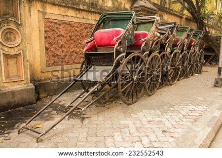 Traditional hand pulled Indian rickshaws parked together in front of a old building in Kolkata - stock photo