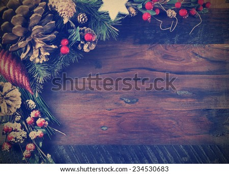 Traditional Happy Holidays and Christmas background with pine cones and festive ornaments on dark recycled wood with copy space for your text here, with retro vintage filter. - stock photo