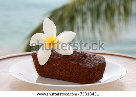 traditional hawaiian banana bread with a hot pink plumeria flower on a white plate outside with the pacific ocean out of focus in the background on the island of maui hawaii - stock photo