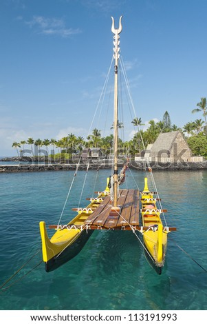Traditional Hawaiian outrigger canoe lit by the early morning sun floating in a clear ocean water. - stock photo