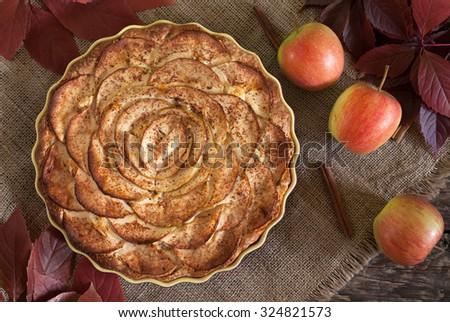 Traditional holiday celebration homemade apple pie sweet dessert food with cinnamon and apples on vintage wooden background. Top view. Autumn decor. Rustic style and natural light. - stock photo