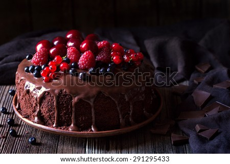 Traditional homemade chocolate cake sweet pastry dessert with brown icing, cherries, raspberry, currant on vintage wooden background. Dark food photo, rustic style, natural light. - stock photo