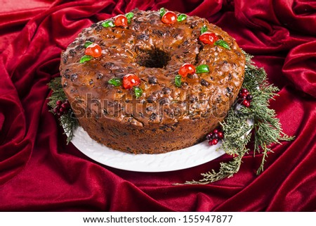 Traditional homemade Christmas fruitcake decorated with candied cherries, boughs and baubles - stock photo
