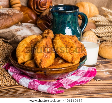 Traditional homemade pies with cabbage and sauerkraut on a plate. Freed Russian pastry pies on a wooden background - stock photo