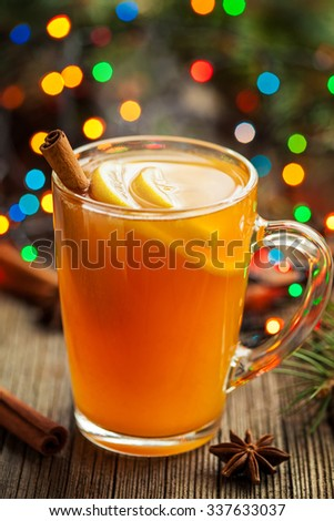 Traditional hot apple cider alcohol drink winter season refreshment juice. Healthy organic christmas or thanksgiving beverage with spices. Hot steam and colorful boke. Vintage wooden background. - stock photo