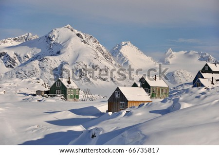 Traditional houses in front of big peak, Kulusuk village, Greenland - stock photo