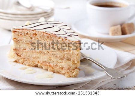 Traditional Hungarian Esterhazy cake with coffee cup and vintage postcards on a white wooden background. - stock photo