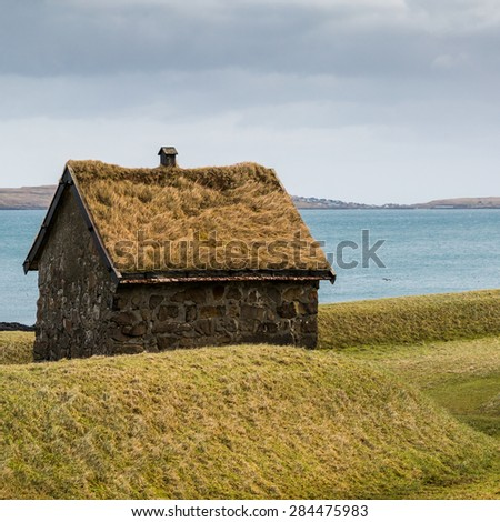 Traditional hut with a green grass roof with a backdrop of the Atlantic ocean and an island - stock photo