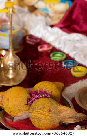 Traditional Indian Hindu religious praying items in ear piercing ceremony for children. Focus on the coconuts. - stock photo