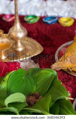 Traditional Indian Hindu religious praying items in ear piercing ceremony for children. Focus on the betel leaves. - stock photo
