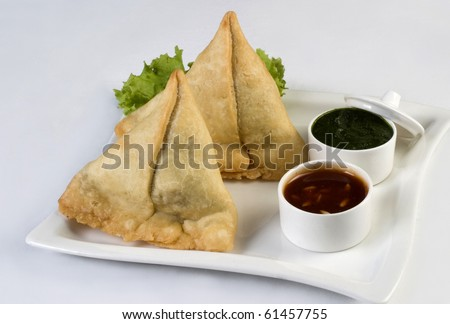 traditional indian snack food samosa with green chutney - stock photo