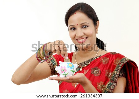 Traditional Indian woman holding a piggy bank and rupee coin-Money saving concept - stock photo