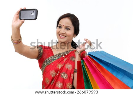 Traditional Indian Woman with shopping bags and take selfie - stock photo
