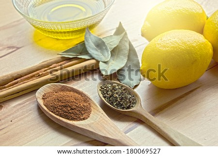 Traditional ingredients cinnamon, lemon and spices on spoons. - stock photo