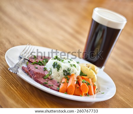 Traditional Irish St. Patricks Day meal of corned beef, potatoes and carrots and a stout beer - stock photo