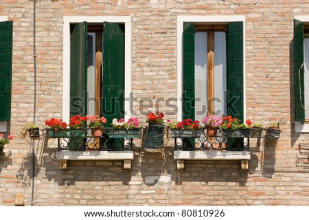 Traditional Italian balconies with perlagonium filled window boxes.  Venice, Italy. - stock photo