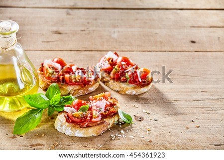 Traditional Italian bruschetta appetizers with spicy savory tomato topping on toasted bread and olive oil garnished with fresh basil served on a rustic wooden table with copy space - stock photo