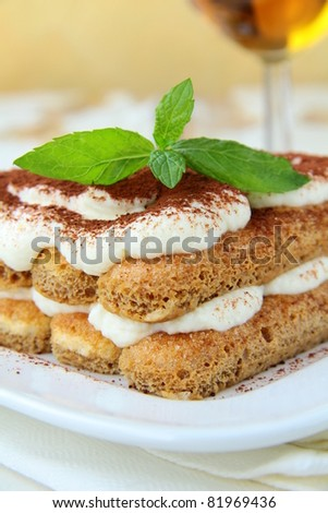 Traditional Italian dessert tiramisu on white plate - stock photo
