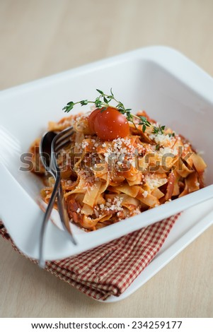 Traditional Italian dish pasta with bolognese sauce made from assorted meat ragu, onion, celery, carrot, garnished with freshly grated parmesan cheese with thyme sprig and cherry tomato - stock photo