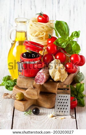 Traditional Italian food. Tagliatelle and salami with fresh tomatoes, cheese, olives and herbs. - stock photo