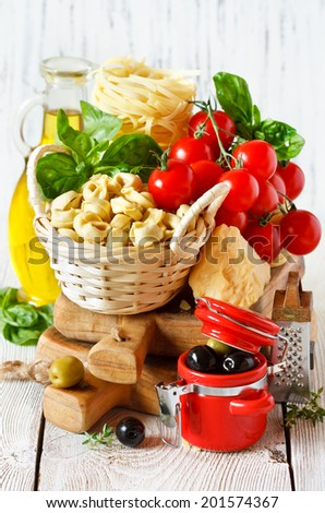 Traditional Italian food. Tagliatelle and tortellini with fresh tomatoes, cheese, olives and herbs. - stock photo