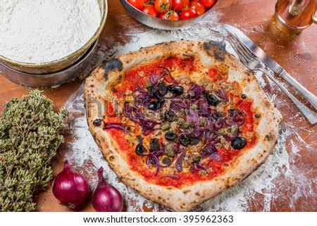 Traditional italian pizza with tuna, onions, caper and olives, on a wooden table with the ingredients - stock photo