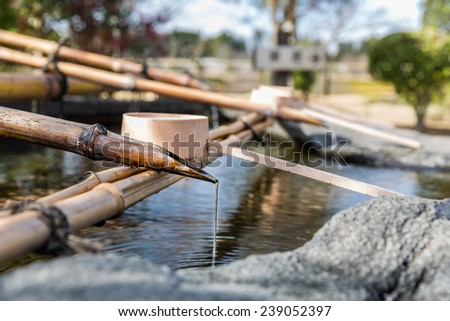 Traditional Japanese bamboo fountain dripping water with ripples in a basin - stock photo