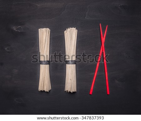 Traditional Japanese buckwheat soba noodles with red chopsticks laid out in a row on wooden rustic background top view close up - stock photo