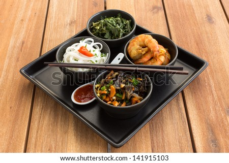 Traditional japanese dish on a square plate in black bowls with shrimp, rice noodles, kale (green cabbage) and fried vegetables. Composed with ceramic spoon with spicy red sauce and chinese chopsticks - stock photo