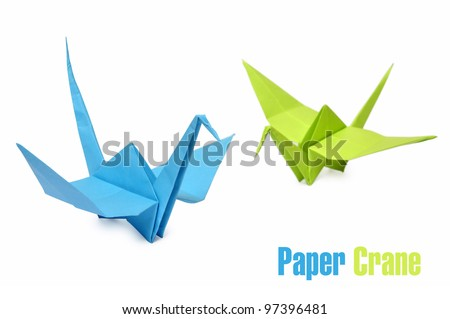 Traditional Japanese origami cranes made from blue and green paper over white background - stock photo