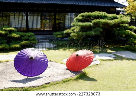 Traditional Japanese red umbrella in Japanese garden  - stock photo