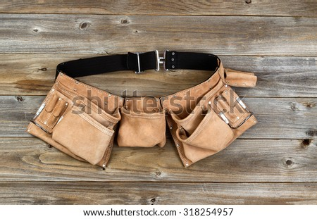 Traditional leather tool belt on rustic wooden floor. - stock photo